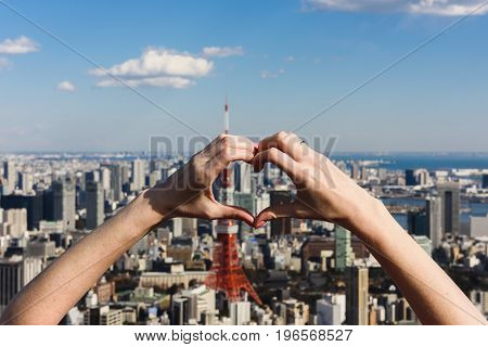 Female hands In form of heart against Tokyo Tower with skyline in Tokyo Japan.