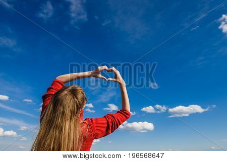 Female hands In form of heart against sky. Bottom view.
