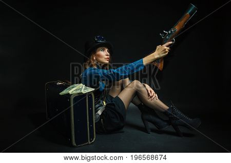 Subculture fashionable victorian elegant weapon concept. Steampunk girl armed and dangerous. Lady dressed in victorian fashion holding antique firearm aiming.