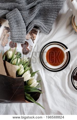 A cozy photo. Top view of a cup of tea and a bouquet of white tulips in black paper