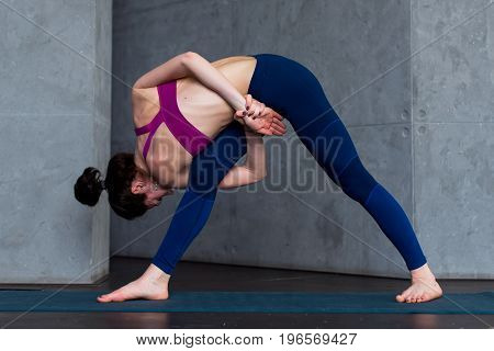 Sporty Caucasian woman practicing standing side angle twist position during yoga class.