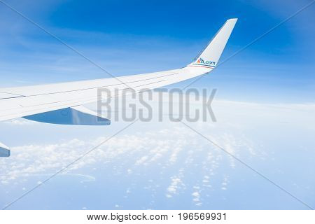 Florida, USA - July 9, 2012; AA.com red and blue brand on aircraft wing above cloud and against blue sky.