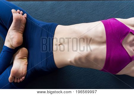 Close-up image of slim female body in sports bra and leggings lying on mat barefoot doing backbend with legs crossed in lotus position.