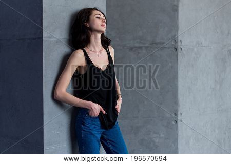 Skinny young European female model in casual clothes posing standing relaxed leaning on wall looking away from camera.