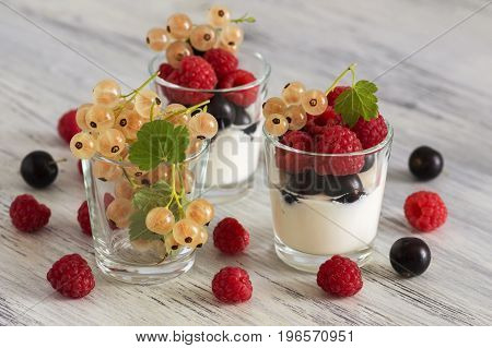 Sour cream in a glass with raspberries and currants. Assorted berries with sour product