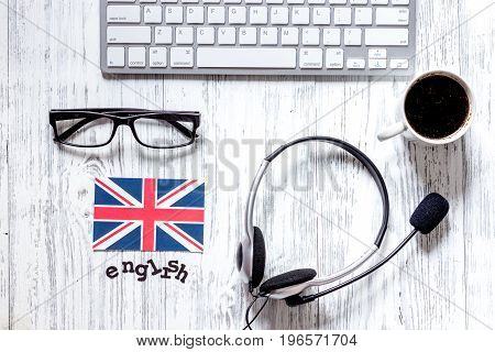 Self-education. Learning english online. Headphones and keyboard on wooden table background top view.