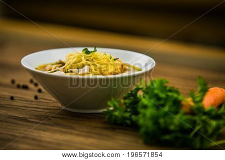 Chicken soup with noodles and fresh vegetables in bowl