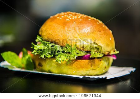 Sandwich hamburger with and mix of vegetables.