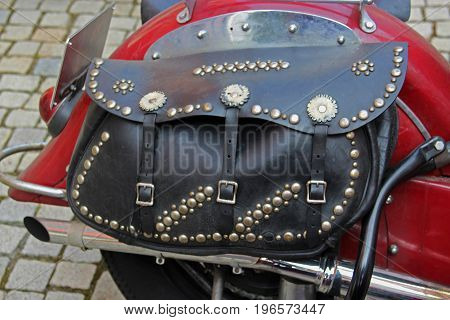 black leather bag with lots of rivets on an old red motorcycle standing on pavement