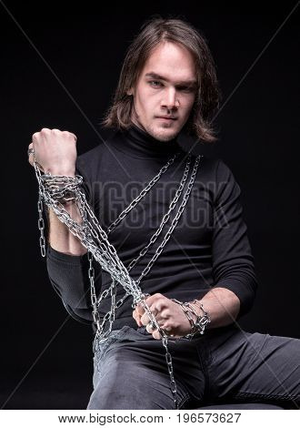 Brunette young man and shackles on black background