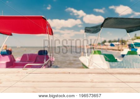 Summer blurry background quay catamarans and blue cloudy sky