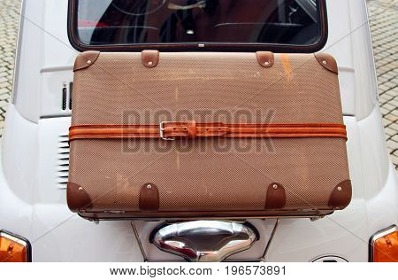 little old white car with a brown vintage suitcase strapped on its back
