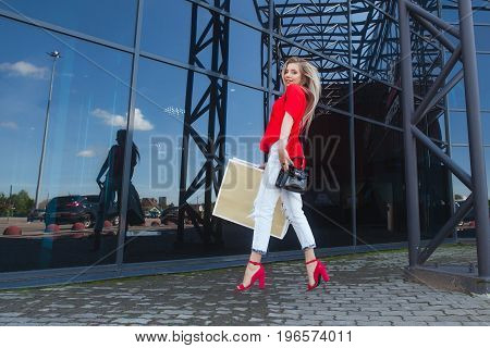 Portrait of jumping beauty fashion smiling woman with shopping bags in red shirt near shopping center. Outdoors. Copy space