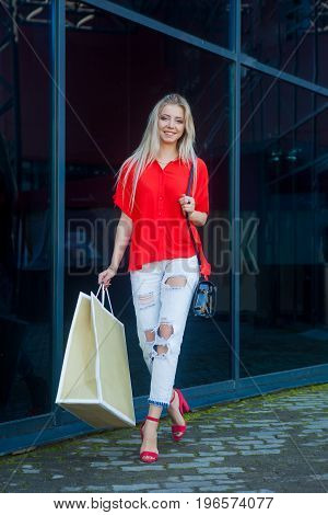 Portrait of beauty fashion smiling woman with shopping bags in red shirt near shopping center . Outdoors. Copy space