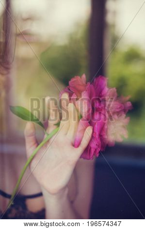 Image of young woman holding peony flower. Femininity and sensuality concept.