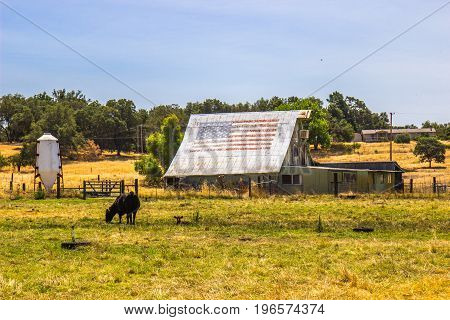 Vintage Wooden Barn With American Flag On Tin Roof