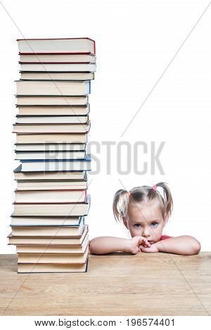 Portrait of a sad little girl leaning on a table with a big pile of books, isolated on a white background
