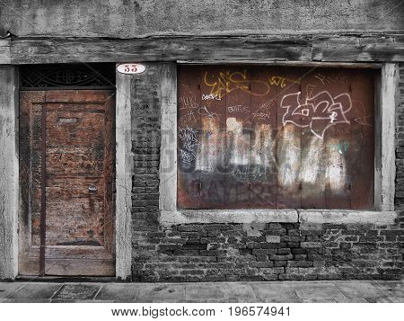 derelict decaying shop building with boarded up window and vandalism
