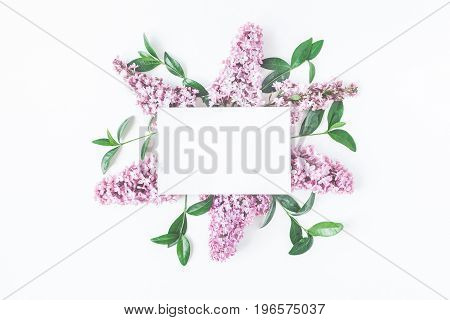 Flowers mock up. Pink lilac flowers green leaves and paper blank on white background. Flat lay top view copy space