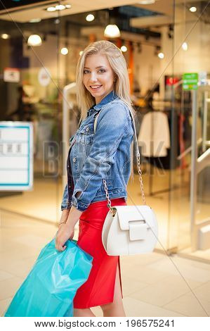 Concept Shopping. Portrait of beauty blonde smiling woman in casual clothes holding shopping bags near shop in the shopping center.