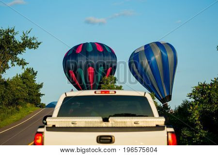 Three hot air ballons holding up traffic as they land next to a Wisconin road in July