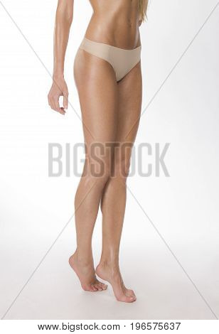 Healthy woman's legs in beige thongs isolated shot