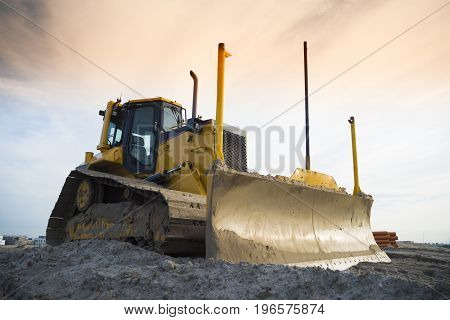yellow excavator on a construction site in front of an orange sky