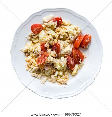 Top view of fried eggs with slices of tomatoes in plate, isolated on white background.