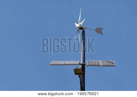 Street lamp with a wind turbine and solar panel a bottom view in the daytime on a dark blue sky.