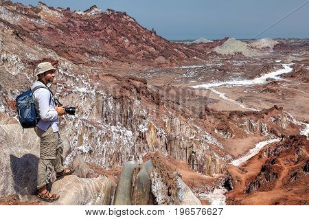 Photographer traveler on foot camping trip up the salty mountains in Hormuz Island Hormozgan Province Iran.