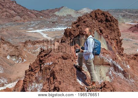 Hormuz Island Hormozgan Province Iran - Tourist hike up the steep track on salty mountains one backpacker admiring the beautiful scenery with a backpack and a camera.