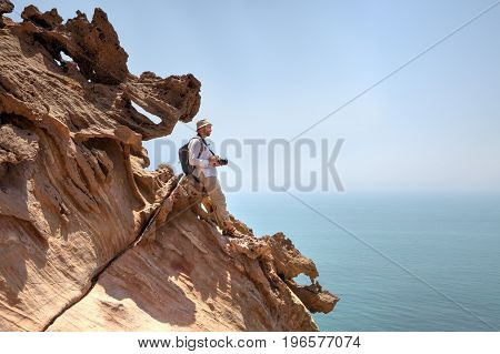 Brown rocks against the blue sea and the lone figure of the traveler's photographer on the edge of the cliff Hormuz Island Hormozgan Province southern Iran.