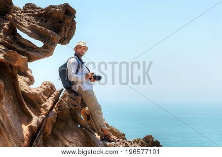 Hormuz Island Hormozgan Province southern Iran traveller with camera sits on the edge of a cliff.