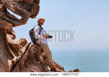 Hormuz Island Hormozgan Province Iran Nature photographer standing on edge of cliff above the sea.
