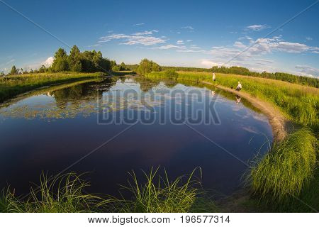 Fishing on the lake with lilies in rural location. Fishermen catch fish. On a Sunny summer day. White clouds on blue sky. Reflection of clouds in the beautiful blue water of the lake. Bright green grass and trees. Beautiful natural landscape.