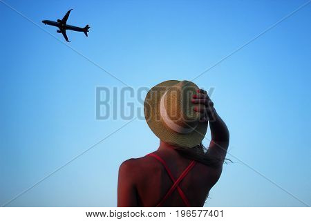 Young beautiful girl looking up at the sky where the plane is flying away.