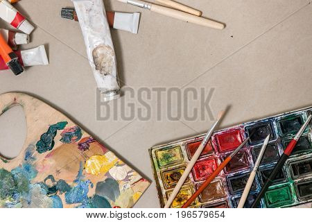 Artistic set for painting with palette of paint swatches, brushes and watercolor paints. Top view of painter's tools on gray background with free space