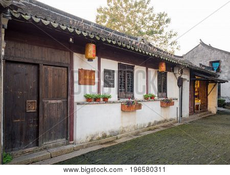 Suzhou, China - Nov 5, 2016: Stores at the historic Zhouzhuang Water Town. Two classical lanterns are hung outside stores.