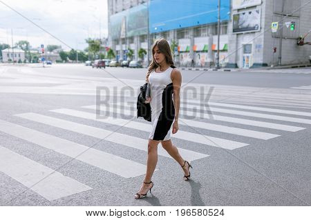 Young fashionable passersby in metropolis. Stylish girl crossing road