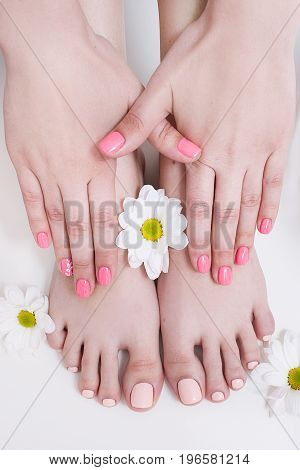 Nude manicure and pedicure for summer. Female hands and feet on white background top view. Result of spa salon procedure