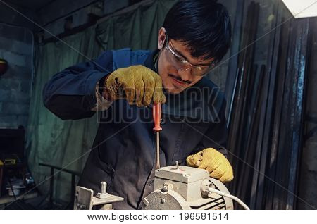 Young handyman repair motor with screwdriver in home