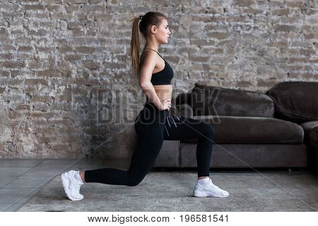 Profile view of sporty girl doing lunges working-out leg muscles and glutes in loft interior.