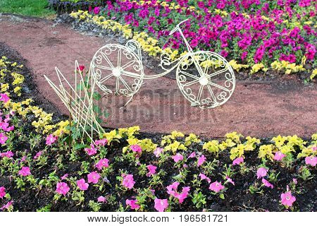 Decorative bicycle on a flower bed in the park