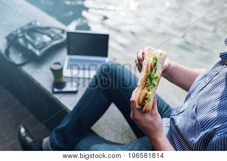 Male workaholic business lunch with junk food outdoors. Modern technology, unrecognizable businessman