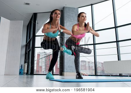 Smiling young girlfriends practicing yoga together indoors. Two slim sporty women standing in one-legged chair pose called Utkatasana
