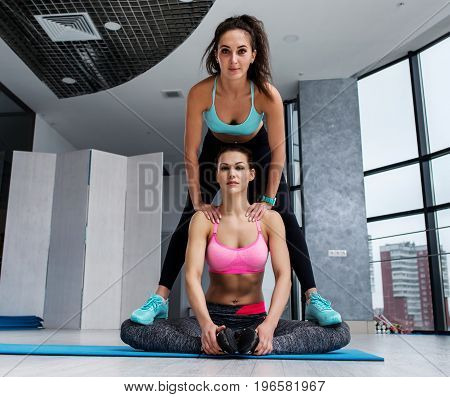Pretty young tanned woman helping her friend standing on her knees while she s doing adductor stretching exercise sitting feet together on mat