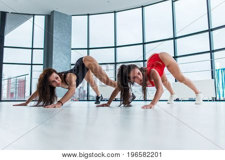 Sporty young women attending gymnastics classes. Female athletes stretching back and legs standing on tiptoe and crawling forward arching back in studio.