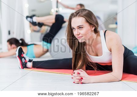 Cute smiling young lady in sportswear doing advanced middle split exercise bending over leaning on arms in gym.