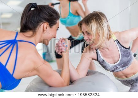 Two strong female friends having fun laughing arm-wrestling on exercise ball in gym.