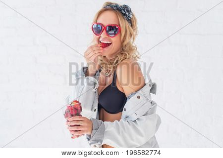 Woman eating strawberries laughing looking at camera wearing sunglasses heart shape in lingerie and jeans jacket Beautiful happy model standing near wall Style fashion lifestyle